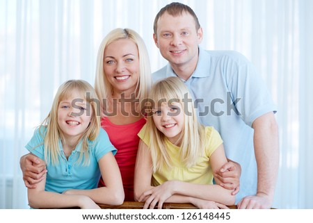 Portrait of happy couple with twin daughters looking at camera at home