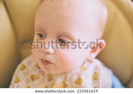 Portrait Of Happy Curious Young Baby Boy Eating Porridge - stock photo