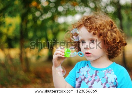 Portrait of happy curly little girl blowing soap bubbles