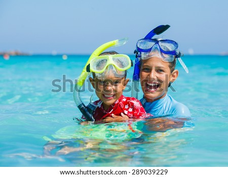 Portrait of happy cute boy and girl wearing snorkeling mask ready to dive in the sea - stock photo
