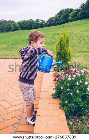 Portrait of happy cute boy watering flowers in the garden with a blue watering can - stock photo