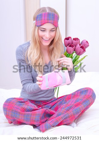 Portrait of happy cute female sitting on the bed in the morning and curiously open little gift box which receive in Valentine day, romantic holiday concept - stock photo