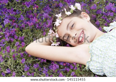 Portrait of happy cute girl wearing garland crown lying on field of flowers - stock photo