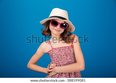 Portrait of happy cute little girl in hat and sunglasses posing over blue backgound - stock photo