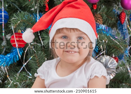 Portrait of happy cute little girl in red Santa hat smiling near the Christmas tree. New Year. - stock photo