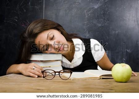 portrait of happy cute real teen student in classroom at blackboard fall asleep - stock photo