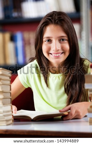 Portrait of happy cute schoolgirl sitting at table in library