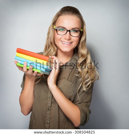 Portrait of happy cute student girl with books in hands over gray background, enjoying first days of education in high school - stock photo
