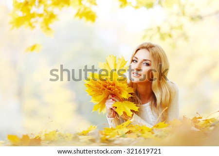 Portrait of happy cute woman holding in hands bunch of dry maple leaves in autumn park - stock photo