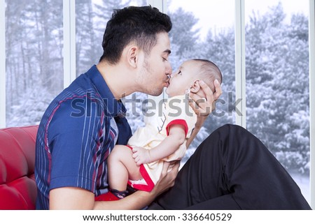 Portrait of happy dad sitting on sofa while holding and kissing his little son, shot with winter background on the window - stock photo