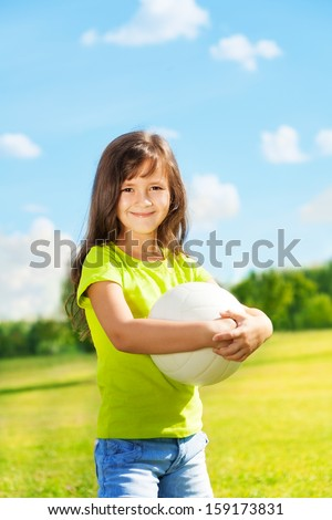 Portrait of happy dark girl with long hair standing with ball outside - stock photo