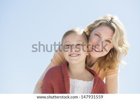 Portrait of happy daughter and mother against clear blue sky - stock photo