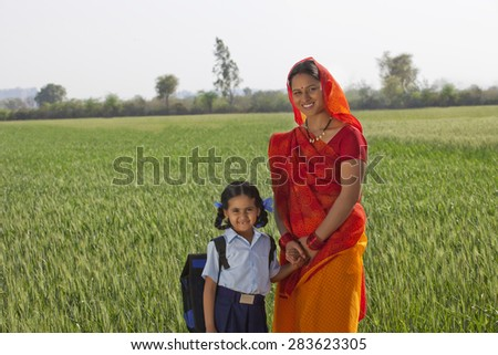 Portrait of happy daughter and mother standing together with field in background - stock photo