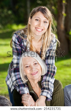 Portrait of happy daughter embracing mother at campsite - stock photo