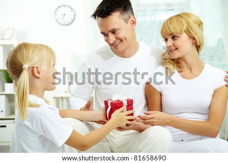 Portrait of happy daughter taking giftbox from parents hands on her birthday - stock photo