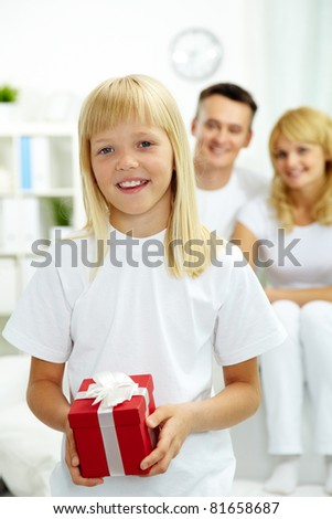 Portrait of happy daughter with giftbox looking at camera with parents on background - stock photo