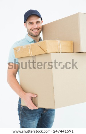 Portrait of happy delivery man carrying cardboard boxes on white background