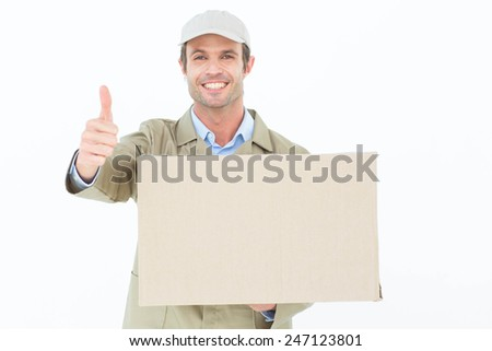 Portrait of happy delivery man gesturing thumbs up while carrying cardboard box over white background - stock photo