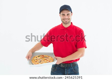 Portrait of happy delivery man holding fresh pizza on white background