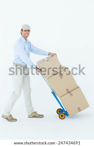 Portrait of happy delivery man pushing trolley of cardboard boxes over white background - stock photo