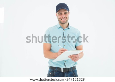 Portrait of happy delivery man writing on clipboard against white background - stock photo