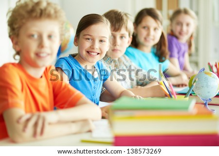 Portrait of happy diligent pupil looking at camera among her classmates at lesson - stock photo