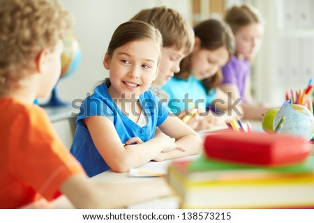 Portrait of happy diligent pupil looking at her classmate at lesson - stock photo