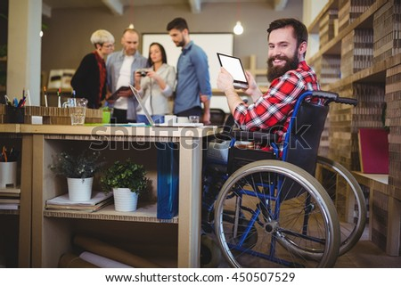 Portrait of happy disabled businessman using digital tablet at desk in creative office - stock photo