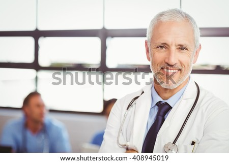 Portrait of happy doctor smiling in conference room in hospital - stock photo