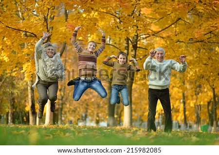 Portrait of happy elderly couple and children jumping in autumn park - stock photo
