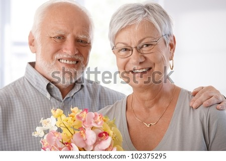 Portrait of happy elderly couple with flowers, looking at camera. - stock photo