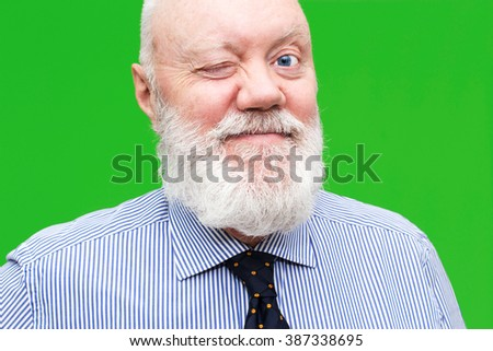 Portrait of happy elderly man posing on green background with wink, color and contrast manipulated - stock photo