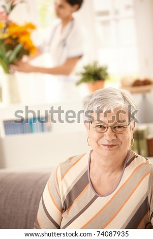 Portrait of happy elderly woman sitting on sofa at home, nurse arranging flowers in background.? - stock photo