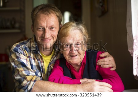 Portrait of happy elderly woman with adult grandson. - stock photo