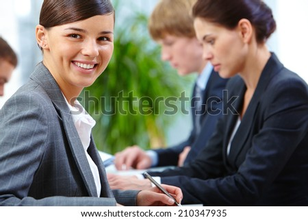 Portrait of happy employee looking at camera on the background of her colleagues - stock photo