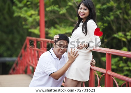 Portrait of happy expecting couple in the nature - stock photo