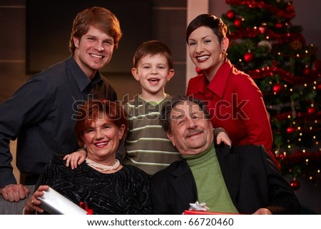 Portrait of happy family at christmas eve, looking at camera, smiling.? - stock photo