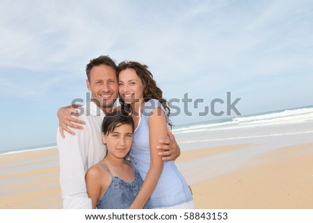 Portrait of happy family at the beach - stock photo