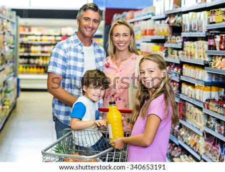 Portrait of happy family at the supermarket - stock photo