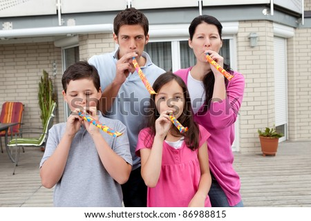 Portrait of happy family blowing whistle and having fun in backyard