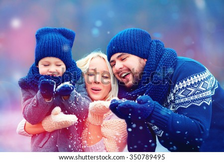 portrait of happy family blowing winter snow - stock photo