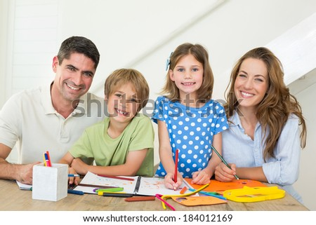 Portrait of happy family drawing together at table - stock photo
