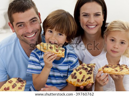 Portrait of happy family eating pizza in living-room all together - stock photo
