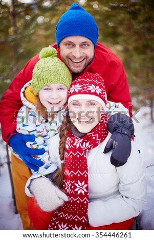 Portrait of happy family embracing outdoors - stock photo