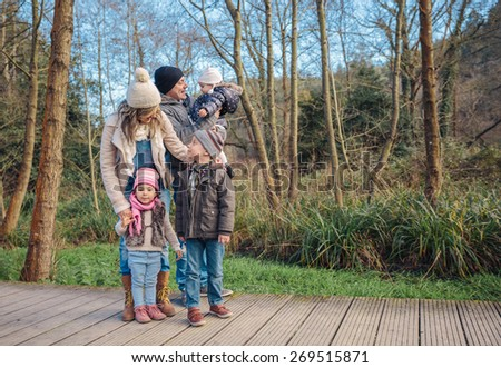 Portrait of happy family enjoying together leisure over a wooden pathway into the forest. Family time concept. - stock photo