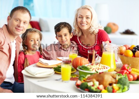 Portrait of happy family gathered at festive table on Thanksgiving Day