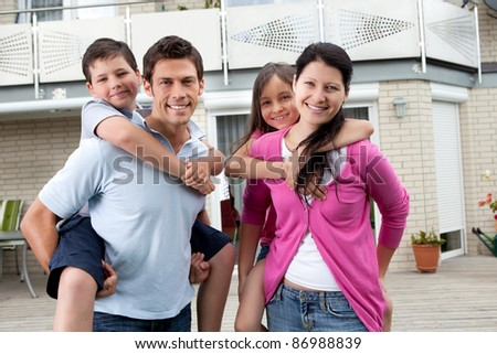 Portrait of happy family having fun outdoors at their home - stock photo