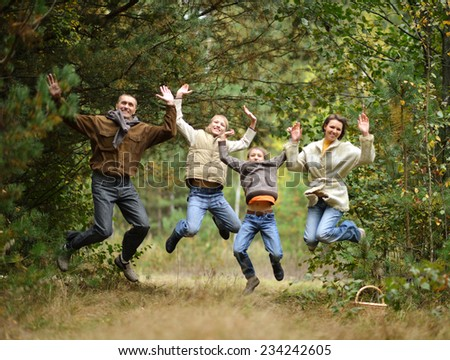 Portrait of happy family in autumn forest - stock photo