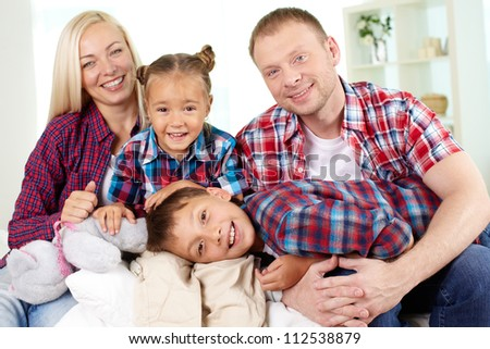 Portrait of happy family in shirts looking at camera at home