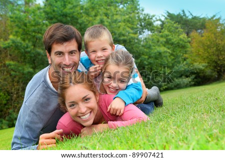 Portrait of happy family laying in country field - stock photo